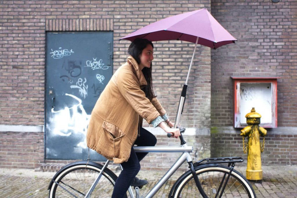 Driving A Bike Holding An Umbrella
